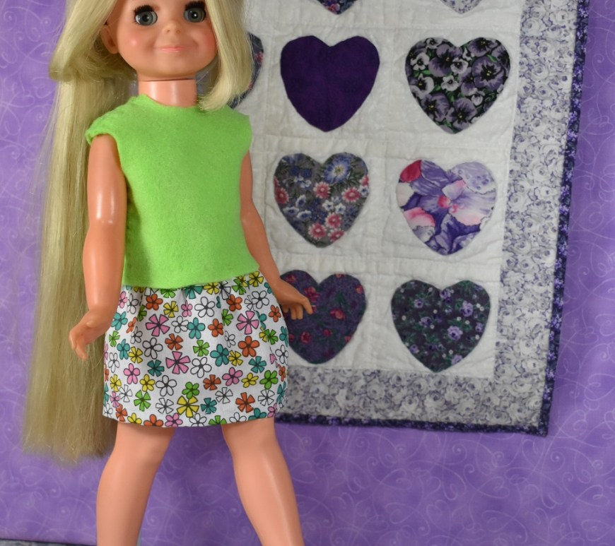 """The image shows a 16"""" Velvet doll from the Crissy family of vintage dolls. She seems to be strolling in front of a wall where a lovely miniature quilt is hanging. The quilt is made with purple applique hearts on a white background, and it's trimmed in purple and white floral fabric. The doll wears an easy-to-sew felt sleeveless shirt / top and a super easy to make elastic waist skirt. Patterns for the skirt and shirt are found at ChellyWood.com in the form of a free printable PDF sewing pattern."""