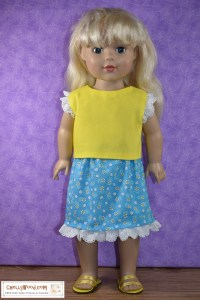 "Here we see an 18"" doll (similar in body style to the American Girl doll) modeling a pretty yellow top with eyelet lace trim around the sleeves and a bright blue skirt decorated with yellow and white daisies in the fabric's printed design. The skirt is trimmed with the same white eyelet lace that we see at the sleeves of the shirt. Click on the link in the caption, and it will take you to a page where you can download and print all the free printable sewing patterns for making these doll clothes, along with links to tutorial videos that show you how to make this outfit."