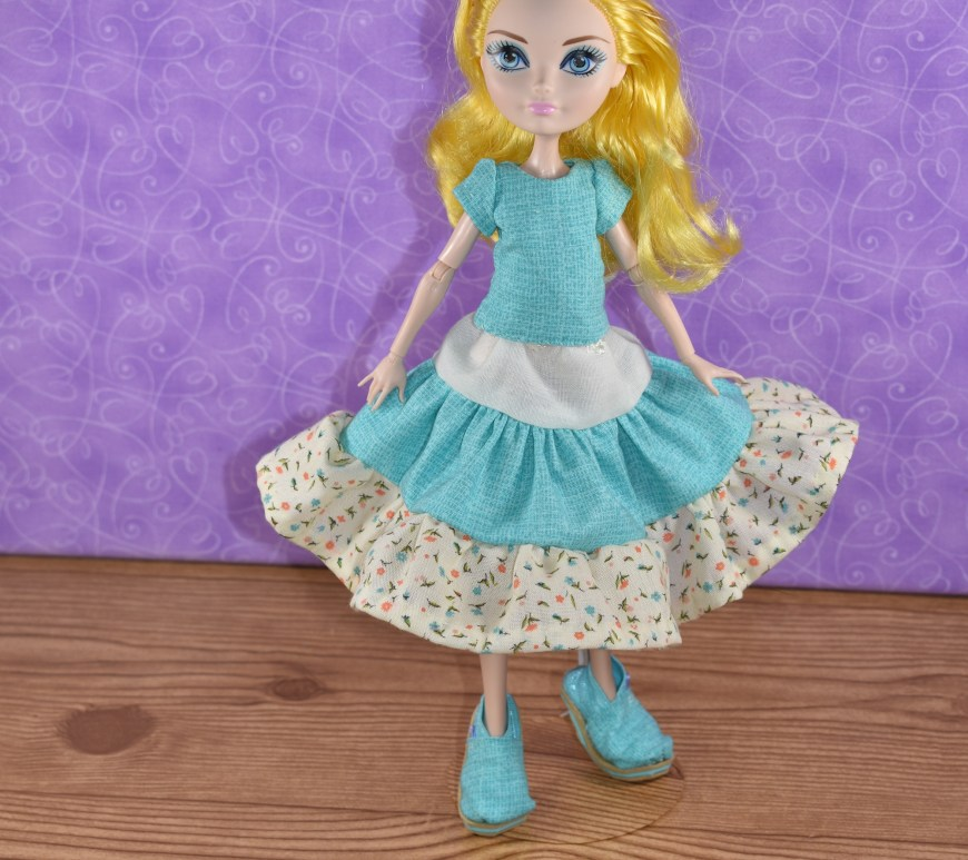 The image shows a Monster High or Ever After High doll wearing a handmade outfit which looks very gypy-like. It includes shoes that look like Toms (handmade), a 3-tier skirt in three different colors of fabric, and a handmade short-sleeved shirt.
