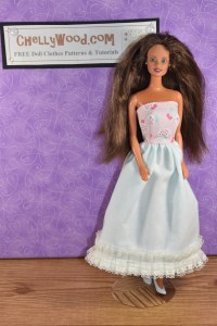 "Here we see a vintage Barbie doll with a 1980's ""Teresa"" head that has long brown hair. The doll is wearing a strapless dress with a pink bodice, a white skirt, and at the bottom of the skirt, the ball-gown-style long dress is trimmed in square-pattered lace. This dress could be worn for a prom or as a wedding dress."