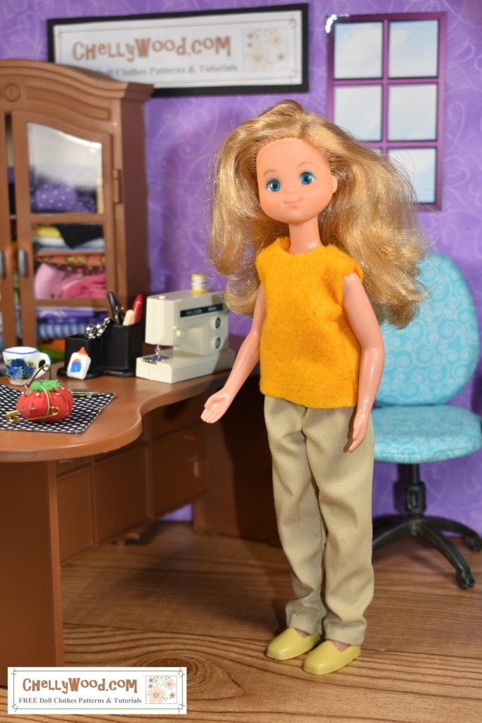 """The image shows a 1970's Sunshine Family """"mom"""" doll wearing an easy-to-sew felt shirt with elastic-waist khaki pants. She stands in a sewing room. The desk beside her has a Galoob sewing machine on it, along with a tiny tomato-shaped pin cushion, a bottle of glue, a coffee cup, and some fabric. If you'd like to make this or other doll clothes for your Sunshine Family doll, please go to ChellyWood.com (or just click on the link in the caption and it will take you to the page where these doll clothes' patterns are available on the Chelly Wood free doll clothes patterns website)."""