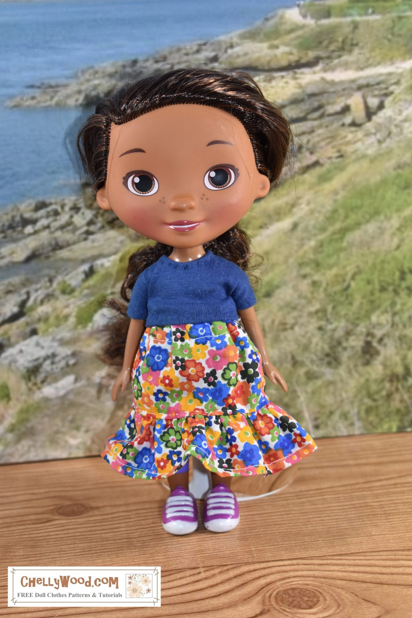 With a rocky beach behind her, we see a Doc McStuffins doll here, modeling a handmade short-sleeved T-shirt and an elastic-waist skirt with a ruffle. The skirt's fabric is decorated with hundreds of tiny bright-colored flowers in a retro style. Click on the link in the caption, and it will take you to a page where you can download and print all the free printable sewing patterns for making these doll clothes, along with links to tutorial videos that show you how to make this outfit.