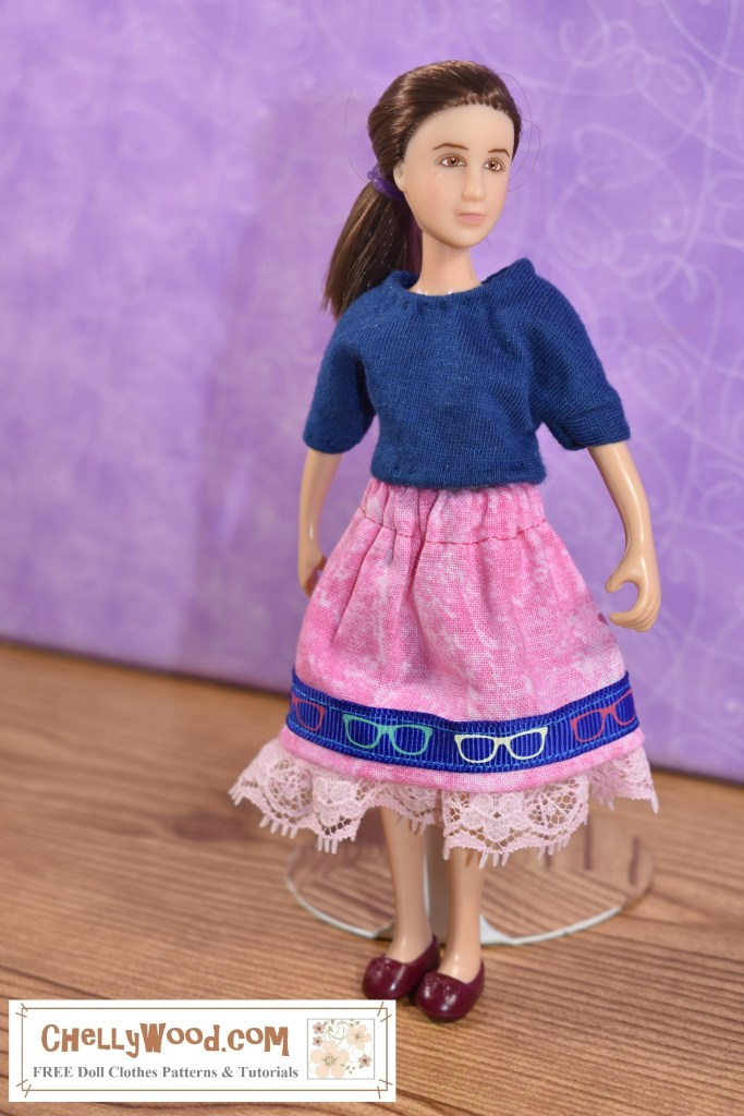 """The image shows a 6"""" Classic Breyer rider doll modeling a handmade navy blue T-shirt with an elastic-waist skirt that has a lace trim at the bottom and a blue ribbon along the hem of the skirt. The blue ribbon is decorated with a tiny print that looks like sunglasses. Please click on the link in the caption to find the free printable PDF doll clothes sewing patterns provided at ChellyWood.com for making this outfit."""