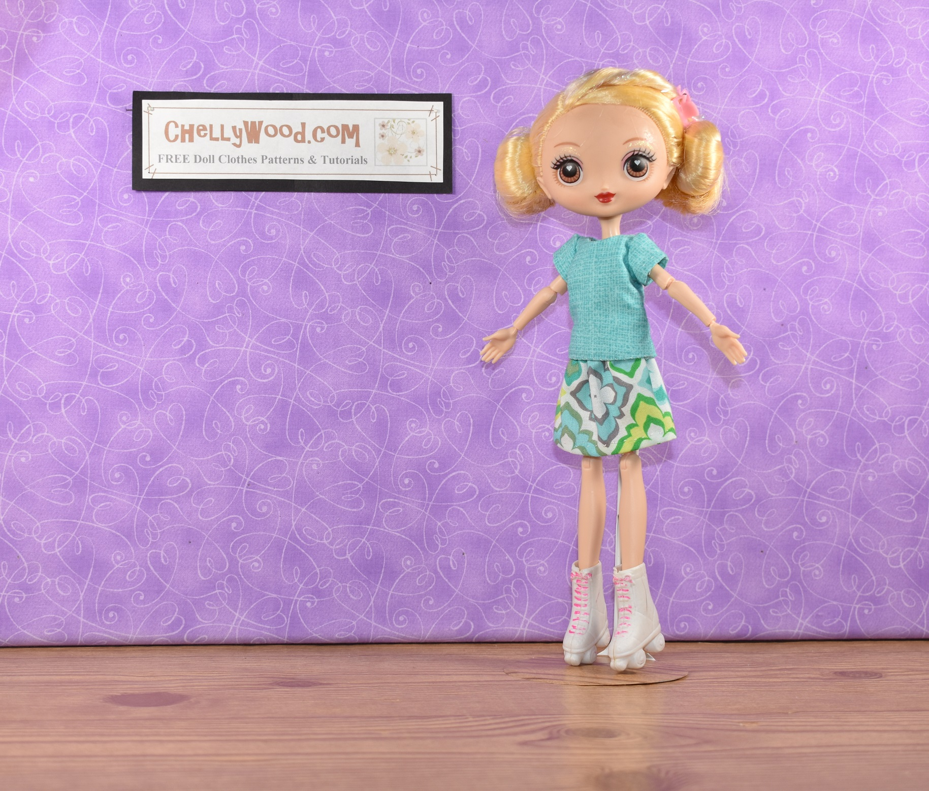 If you're here to find the free patterns for sewing doll clothes to fit your Kuu Kuu Harajuku fashion dolls, please click on the link in the caption. The image shows a Kuu Kuu Harajuku G doll wearing a handmade skirt and matching handmade cotton shirt. The doll wears roller skates, and she has a pink hair clip holding her bangs back. Her enormous eyes look straight at the camera, and the wall behind her tells where you can download the free patterns for sewing this skirt and top: ChellyWood.com