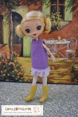With an Italian cafe scene painted on the wall behind her, this Kuu Kuu Harijuku doll models a felt dress with eyelet trim that's super easy for even a beginning sewist to make by hand or on a sewing machine. This dress is simple with a sleeveless design. The doll looks adorable in it, wearing a pair of yellow rain boots as she leans forward as if to splash in a puddle. Click on the link in the caption, and it will take you to a page where you can download and print all the free printable sewing patterns for making these doll clothes, along with links to tutorial videos that show you how to make this outfit.