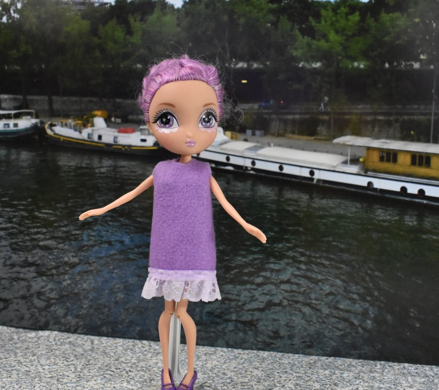 Here we see a La Dee Dah doll standing on a dock or sidewalk overlooking the Seine River in Paris. Behind her is the Eiffel Tower and several boats are docked along a tree-lined warf on the other side of the river. The doll wears a purple felt dress with no sleeves and an eyelet trim. She has her arms splayed out at her sides as if she's going to spin in a circle. The doll's pretty purple hair matches her purple felt dress! Click on the link in the caption, and it will take you to a page where you can download and print all the free printable sewing patterns for making these doll clothes, along with links to tutorial videos that show you how to make this outfit.