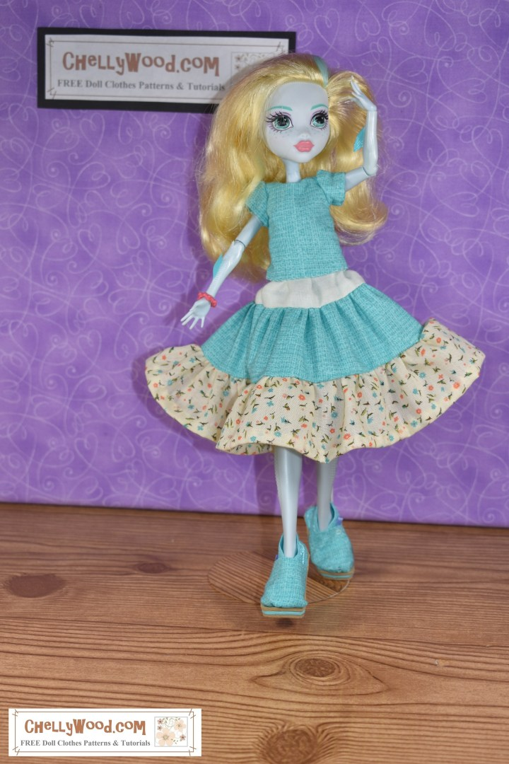 The image shows a Monster High or Ever After High doll wearing a handmade outfit which looks very gypy-like. It includes shoes that look like Toms (handmade), a 3-tier skirt in three different colors of fabric, and a handmade short-sleeved shirt. The camera angle is from front and a bit to the left. The Monster High doll is Laguna Blue, and she holds one hand to her hair.