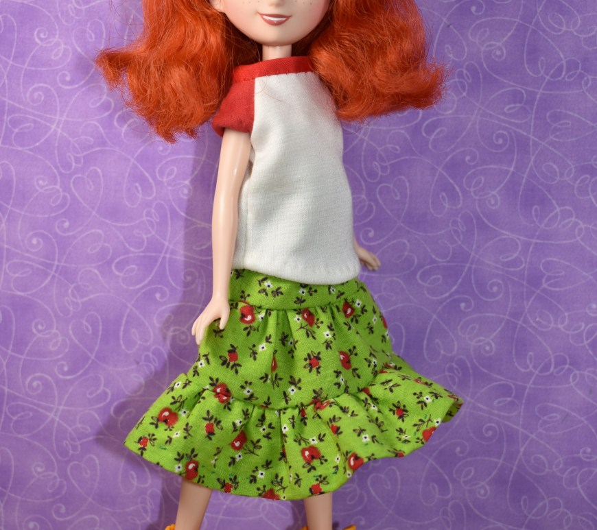 Here we see a Merida Disney Princess doll walking along in a Raglan-sleeve tee shirt and a 3-tier layered skirt with ruffly edge. Her skirt is green with tiny red apples on it. Her shirt is white with little red sleeves and a red collar. Her boots are bright yellow with tiny laces. Click on the link in the caption, and it will take you to a page where you can download and print all the free printable sewing patterns for making these doll clothes, along with links to tutorial videos that show you how to make this outfit.