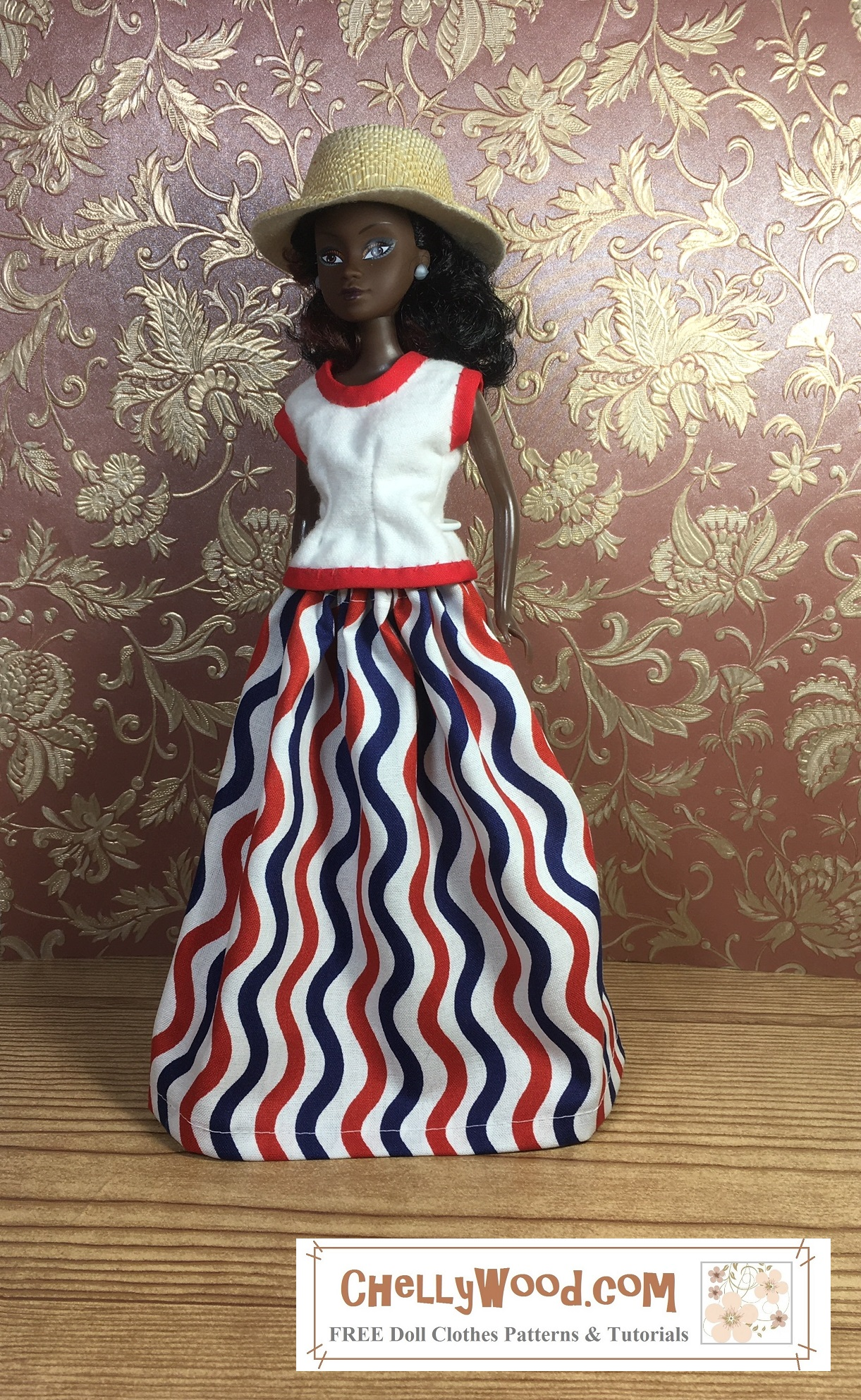 A lovely African or African-American doll with black hair and chocolate complexion stands before a gold-leafy wallpaper on a hard wood floor. She wears a straw hat and a long skirt with sleeveless top. The long skirt is made of a red, white, and blue wavy-patterned flag-like fabric. The sleeveless top is white with red bias tape trim. This doll appears to look a lot like a Barbie doll. Click on the link in the caption, and it will take you to a page where you can download and print all the free printable sewing patterns for making these doll clothes, along with links to tutorial videos that show you how to make this outfit.