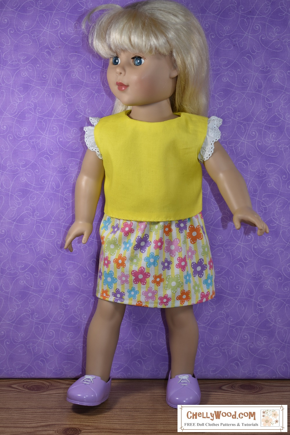 """Here we see an 18"""" doll (similar in body style to the American Girl doll) modeling a pretty yellow top with eyelet lace trim around the sleeves and a multicolored skirt dotted with big colorful daisies in the fabric's printed design. The skirt is an elastic-waist easy-to-sew skirt, ideal for beginners and children learning how to sew for the first time. Click on the link in the caption, and it will take you to a page where you can download and print all the free printable sewing patterns for making these doll clothes, along with links to tutorial videos that show you how to make this outfit."""