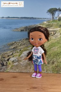 A Doc McStuffins doll stands on a boardwalk overlooking a pretty beach with a distant cottage overlooking a rocky peninsula. Doc McStuffins wears a hand-made t-shirt with handmade shorts. The outfit is embellished with what looks like screen-printed decorations. Click on the link in the caption, and it will take you to a page where you can download and print all the free printable sewing patterns for making these doll clothes, along with links to tutorial videos that show you how to make this outfit.