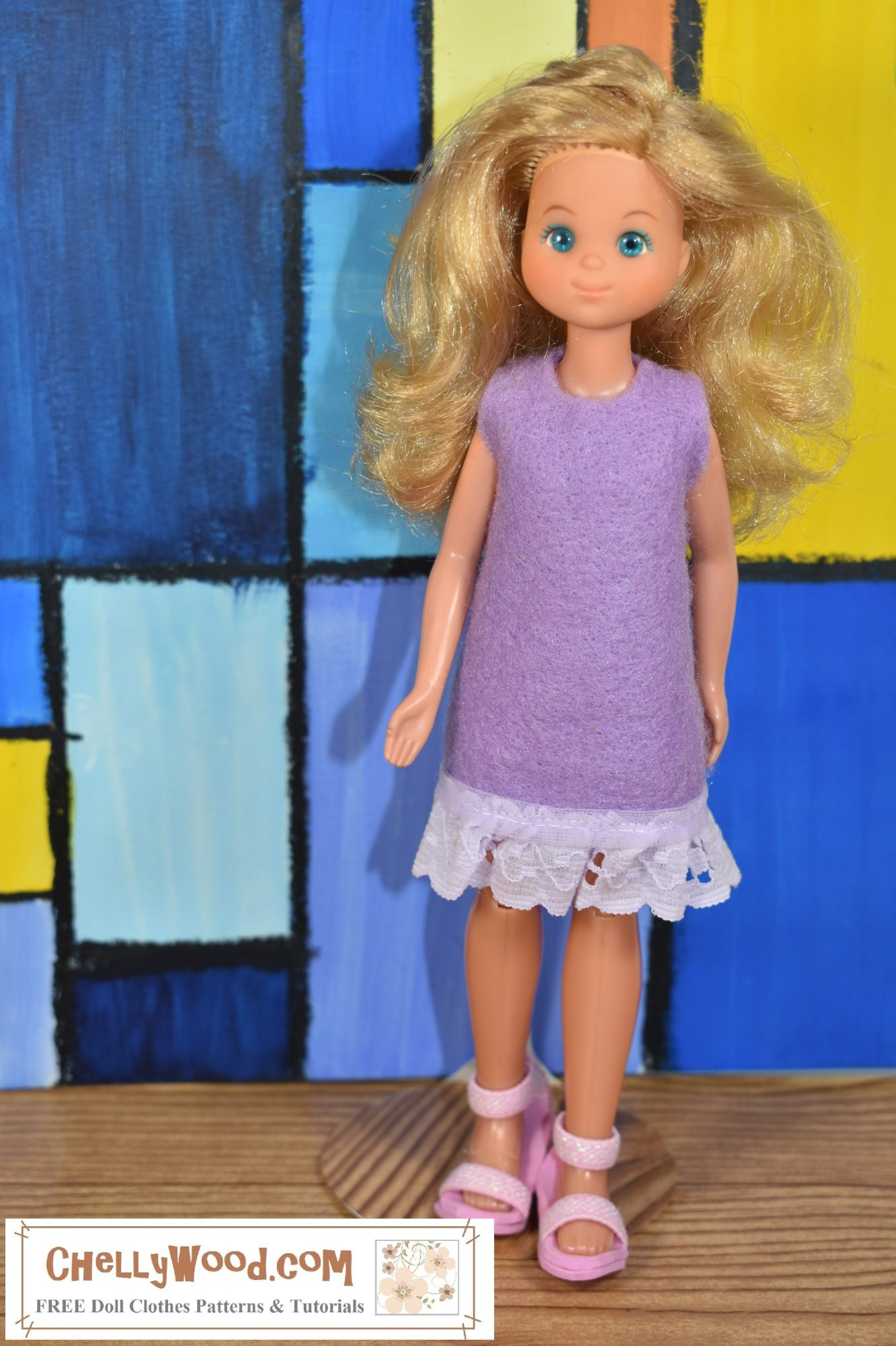 The image shows a vintage Sunshine Family doll wearing a purple felt dress with eyelet lace trim. Please go to ChellyWood.com for the free printable PDF sewing pattern and easy-to-sew tutorial video that will show you how to make this dress (great for beginners and kids learning to sew)! Please click on the link in the caption to navigate to the right page for this pattern and tutorial.