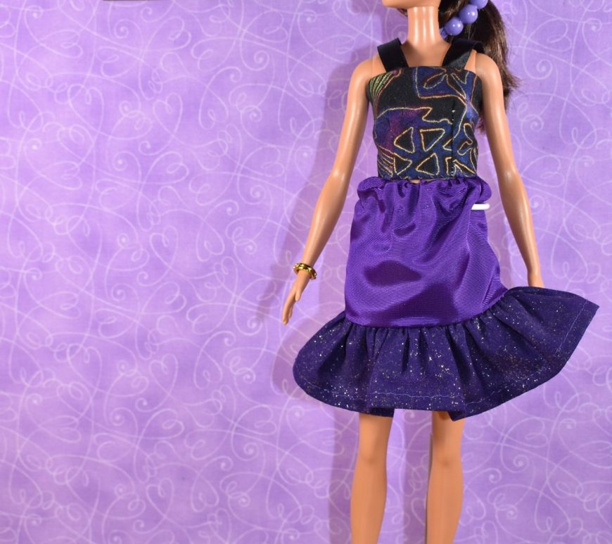 If you're here to download the free printable PDF sewing patterns and to watch the tutorial videos for making this outfit of doll clothes for your Tall Barbie, please click on the link in the description. The photograph is of a Tall Barbie (by Mattel) modeling a handmade set of doll clothes, including an elastic-waist skirt with glittery purple ruffle and a handmade tank top with ribbon straps. The doll appears to be leaning with her weight on her left foot, and the watermark on this image says where you can download this and other free printable doll clothes sewing patterns for making a wardrobe for your tall Barbie dolls: ChellyWood.com