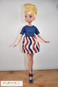 "This is a Tinkerbell Fairy fashion doll from the smaller-than-the-princess-dolls line of Disney character dolls. She wears a handmade crop top T-shirt and a miniskirt of wavy red-white-and-blue cotton fabric. The crop top is made of navy blue jersey fabric that matches the wavy-patterned skirt fabric. The doll also wears navy blue high heel shoes. She looks ""ready to fly away"" as she poses with her arms extended a bit from the bell-shaped skirt. Click on the link in the caption, and it will take you to a page where you can download and print all the free printable sewing patterns for making these doll clothes, along with links to tutorial videos that show you how to make this outfit."