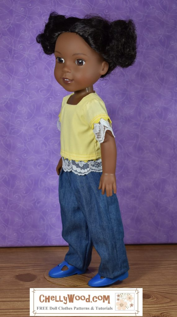 The image shows a Wellie Wisher doll from the American Girl doll company wearing handmade doll clothes. She sports an easy-to-sew pair of elastic waist jeans and a bright yellow square-neck shirt trimmed in rickrack and lace. Click on the link in the caption, and it will take you to a page where you can download and print all the free printable sewing patterns for making these doll clothes, along with links to tutorial videos that show you how to make this outfit.