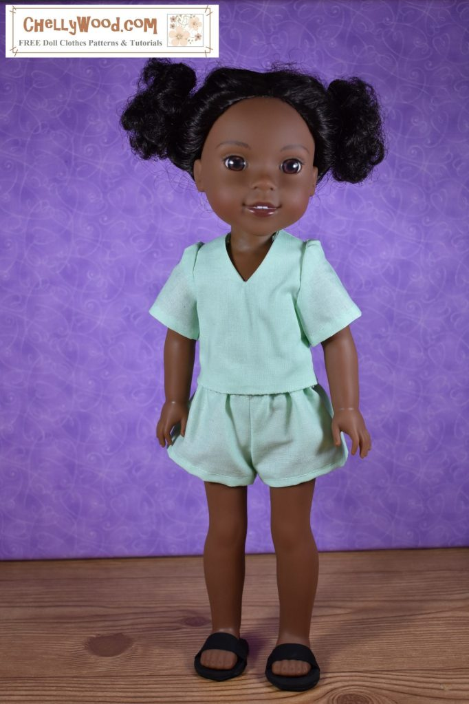 In this image, a Wellie Wisher doll faces the camera in a studio shot. She wears handmade shorts, a handmade shirt with a V-neck collar, and handmade slip-on sandals. Click on the link in the caption, and it will take you to a page where you can download and print all the free printable sewing patterns for making these doll clothes, along with links to tutorial videos that show you how to make this outfit.