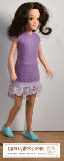 Here we see one of the World of Love female fashion dolls from Hasbro that was produced in the 1970's. She wears a super easy-to-sew felt dress in purple felt with a purple eyelet lace trim. Click on the link in the caption, and it will take you to a page where you can download and print all the free printable sewing patterns for making these doll clothes, along with links to tutorial videos that show you how to make this outfit.