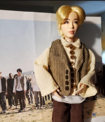 The image shows a BTS doll wearing a vest, shirt with collar, and pants. The image of the real BTS musician is just to the left of the doll. Special thanks to Cindy C for sharing these adorable handmade doll clothes pictures with my followers here on ChellyWood.com -- she used Chelly Wood patterns to make these outfits for the BTS dolls.