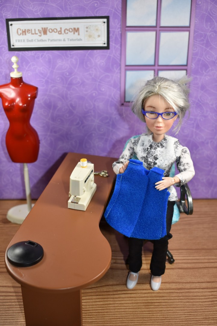 "The image shows the Chelly Wood doll (a Spin Master Liv doll that has had a makeover and hair color changes) seated beside her sewing machine with her mannequin off to the side. She holds up a blue unfinished garment that she seems to have been sewing at the tiny sewing machine. She wears a hand-made long-sleeve shirt, handmade black pants, and white Mary Jane shoes. The doll also wears cat-eye glasses that have slid down the ridge of her tiny nose somewhat. The watermark says ""ChellyWood.com"" (a website for free doll clothes patterns)."