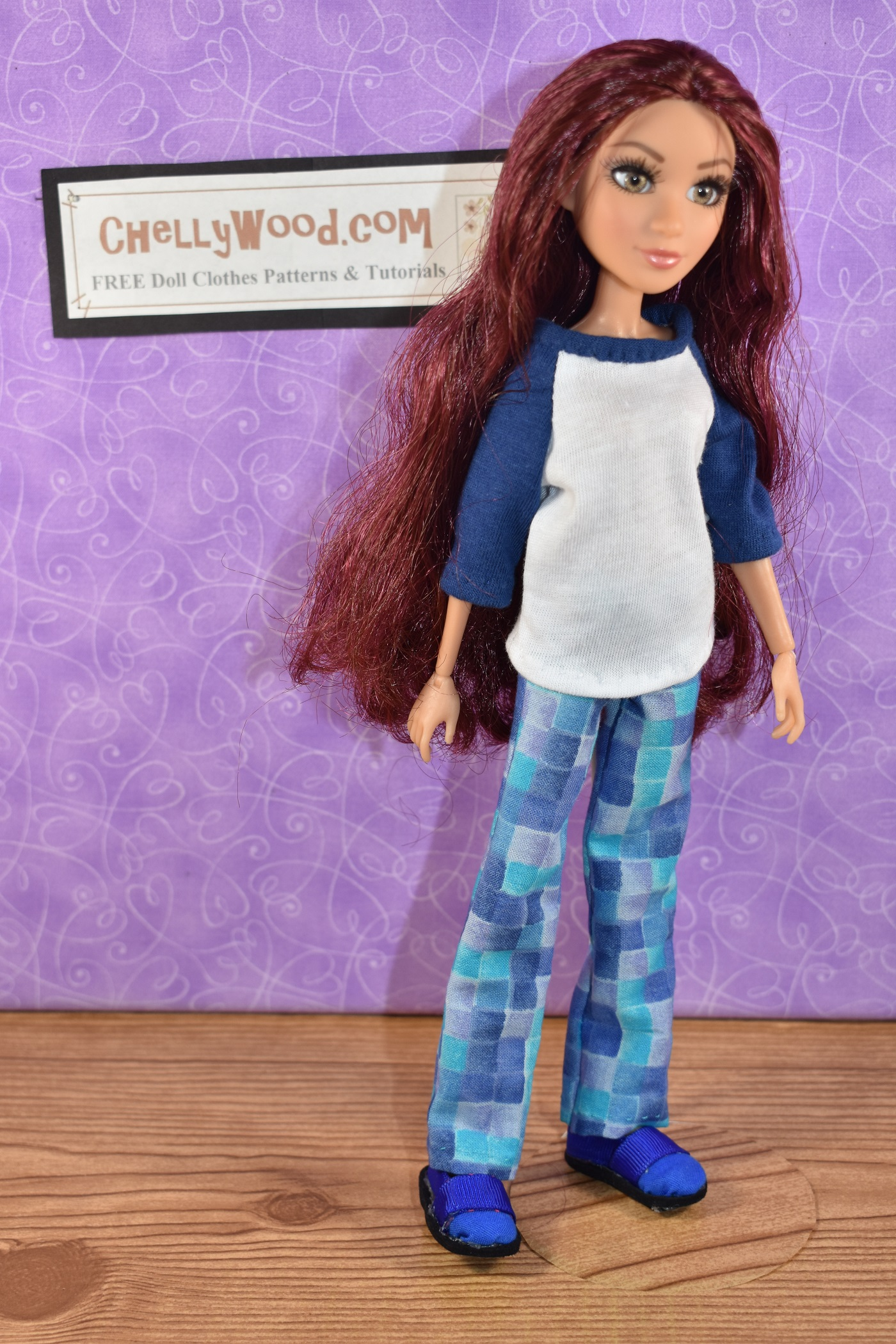 The image shows a Project MC2 Camryn Coyle doll wearing handmade pants and a handmade tee shirt (T-shirt) with the website ChellyWood.com hung on the wall behind her. If you'd like to download and print the free PDF sewing patterns for making these doll clothes to fit your Project MC squared dolls, please click in the link provided in the caption.