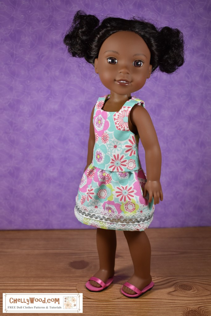 The image shows a Wellie Wisher doll wearing a handmade cotton tank top with a matching bell-shaped skirt. The skirt is trimmed in white lace and silver rick-rack. She also wears a pair of handmade sandals (made of foam and ribbon). If you'd like to make this outfit, please click on the link found in the caption. That link will take you to a page where you can download the free printable sewing patterns and watch the free tutorial videos that show you how to make this whole outfit.
