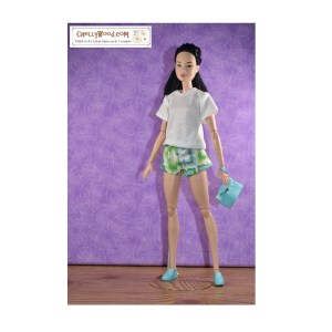 A made-to-move Barbie doll models a pair of handmade elastic-waist shorts in a colorful-patterned fabric with geometric shapes that have a floral feel to them. The colors of the fabric are pale blue, grey, light green, yellow, and white. The doll holds a handmade clutch purse. She wears a simple white t-shirt with a little longer-than-cap sleeves. If you would like the free printable sewing patterns and links to the tutorial videos showing how to make these barbie-sized doll clothes, please visit ChellyWood.com
