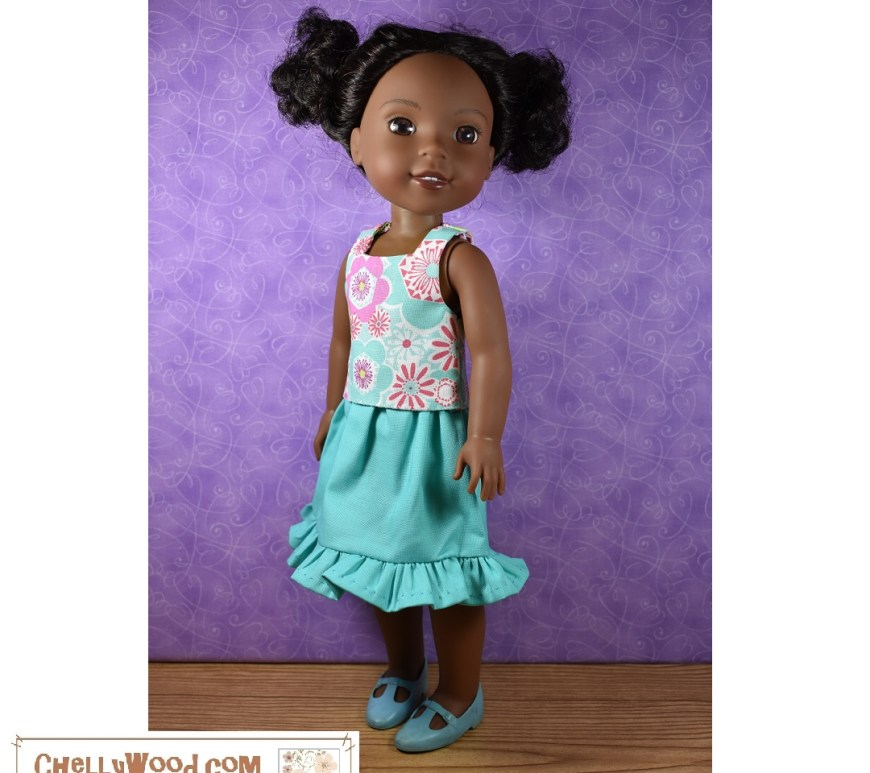 The image shows a Wellie Wisher doll in a turquoise skirt with a pretty ruffle at the bottom and a multi-colored retro-print floral tank top. This image comes from ChellyWood.com, a website with hundreds of free printable PDF sewing patterns and tutorial videos showing how to make each doll clothes item. Visit ChellyWood.com for your free printable PDF sewing patterns for making this outfit to fit Wellie Wishers and other 14 inch dolls.