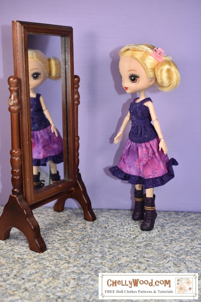 Here we see a 10 inch (25 to 26 cm) Kuu Kuu Harajuku G doll wearing a purple handmade tank top with a pink and purple 3-tier skirt with a ruffle. The doll stands in front of a mirror, and in the mirror, we see the doll's blurred reflection, as though she's looking at her reflection in that mirror.