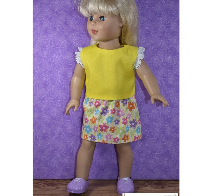 "This is a photo of an 18-inch doll wearing a handmade sunny yellow shirt with an eyelet ruffle sleeve of white eyelet lace. She also wears a multi-colored floral skirt with an elastic waist and an above-the-knee ""schoolgirl"" length. The free printable PDF sewing patterns for making this entire outfit can be found at ChellyWood.com along with hundreds of other free printable sewing patterns for making doll clothes to fit dolls of many shapes and all different sizes."