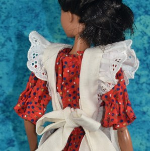The image shows a Mattel modern Barbie wearing a handmade 1970's style dress with elastic sleeves, snaps in the back, and over the top of the dress, she wears a pinafore. In this image, we see the back of the pinafore, which is white (over a red dress). The pinafore straps are edged with eyelet ruffles. The pinafore is drawn into a strappy bow at the back of the dress. The dress itself uses snaps as a closure.