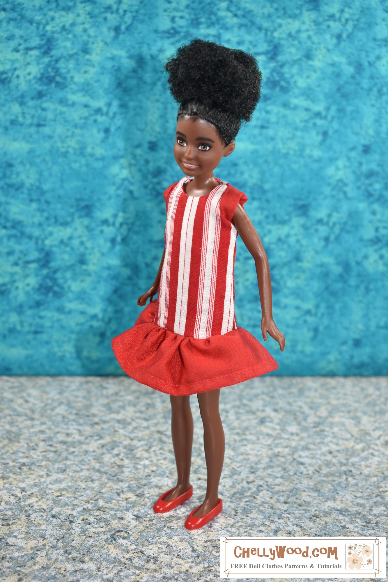 """Click on the link in the caption to navigate to the page where you can make this """"Peppermint Candy"""" dress for your Stacie sized doll, using free printable PDF sewing patterns and tutorials provided by ChellyWood.com. This photo shows Mattel's 9 inch African American Stacie doll wearing a handmade dress, designed and sewn by Chelly Wood, the doll clothing designer, YouTuber, and writer. The dress itself looks a lot like a peppermint candy, with red and white stripes running vertically. There's a solid red ruffle at the bottom of the dress, and this ruffle goes from the dress's dropped waist to just above Stacie's knee. There are also solid red cap sleeves. The doll wears tiny plastic red flat shoes. Her hair is gathered at the top in a very natural looking afro hair style. She looks to her right with her body facing right, and the background is a splotchy turquoise blue which contrasts nicely with the red and white of the handmade dress. For the free printable sewing patterns and tutorial videos to make this dress, please go to ChellyWood.com"""