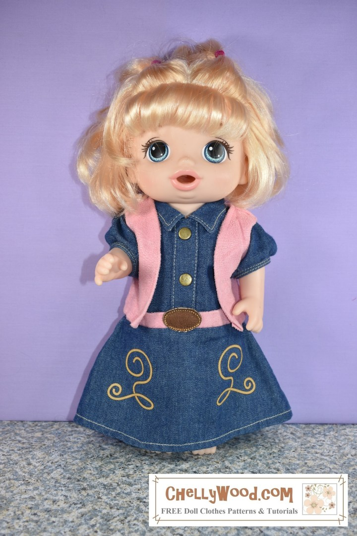 "Here we see a 12 inch Baby Alive doll modeling a western-style ""Cowgirl"" dress with a leather-looking (moleskin) vest and belt. The denim dress is embroidered with tan curly-queues. There are two brass buttons along the faux front closure, and the denim dress does have a nicely-sized collar of about an inch length, folded against the fabric of the bodice. The short sleeves are puffy. The dress is quite long on the doll, reaching almost to the floor she stands on."