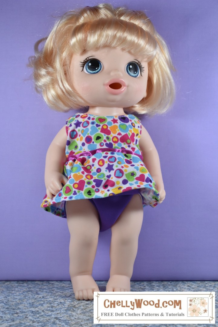 The image shows a 12 inch Baby Alive doll wearing a sleeveless dress that's quite short. The fabric of the dress is patterned with hearts and circles in many bright colors like purple, pink, yellow, and turquoise blue. Under this short dress, you can see a little purple diaper peeking out in a discreet way. The outfit seems to suit the doll in terms of fit, drape, and color.