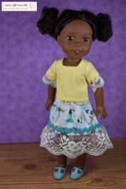 The image shows an African American Wellie Wisher doll wearing handmade clothes that include a short-sleeved shirt with rickrack and lace trim at the sleeves and a mermaid-print skirt with rickrack trim and lace at the bottom of the skirt. The shirt has a square-neck style and is made of creamy yellow cotton. The skirt is sea blue with multi-colored fish and mermaids printed on it (including one with yellow hair), and its rickrack trim is turquoise in color. If you'd like to make this outfit, you can click on the link in the caption, and that link will take you to a page where you can download and print the free PDF sewing patterns for making this outfit. All free patterns and tutorial videos are created and published by ChellyWood.com