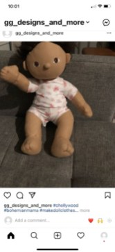 The image shows a Dinkum doll wearing handmade doll clothes that include a T-shirt and shorts made of printed Jersey fabric. The doll appears to be seated on a sofa. This is clearly a screenshot from a person's smartphone, and the page is an instagram page for gg_designs_and_more