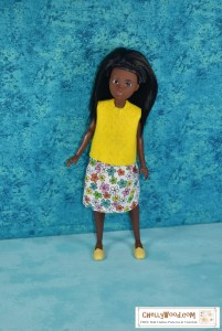 Click on the link in the caption to navigate to the page where you can download and print free PDF sewing patterns for making these doll clothes. The image shows a Black Creatable World doll wearing a handmade felt skirt and an elastic-waist skirt decorated with colorful springtime flowers on a white background. The doll wears yellow loafers, and is posed elegantly with a turquoise blue background behind her.
