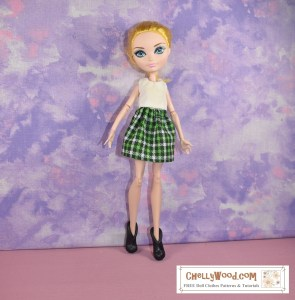 This photo shows an Ever After High doll wearing black plastic shoes, a green and white plaid mini skirt, and a white sleeveless tank top. Her yellow-blond hair is done up in a messy bun. The watermark reminds us to go to ChellyWood.com for free printable doll clothes sewing patterns.