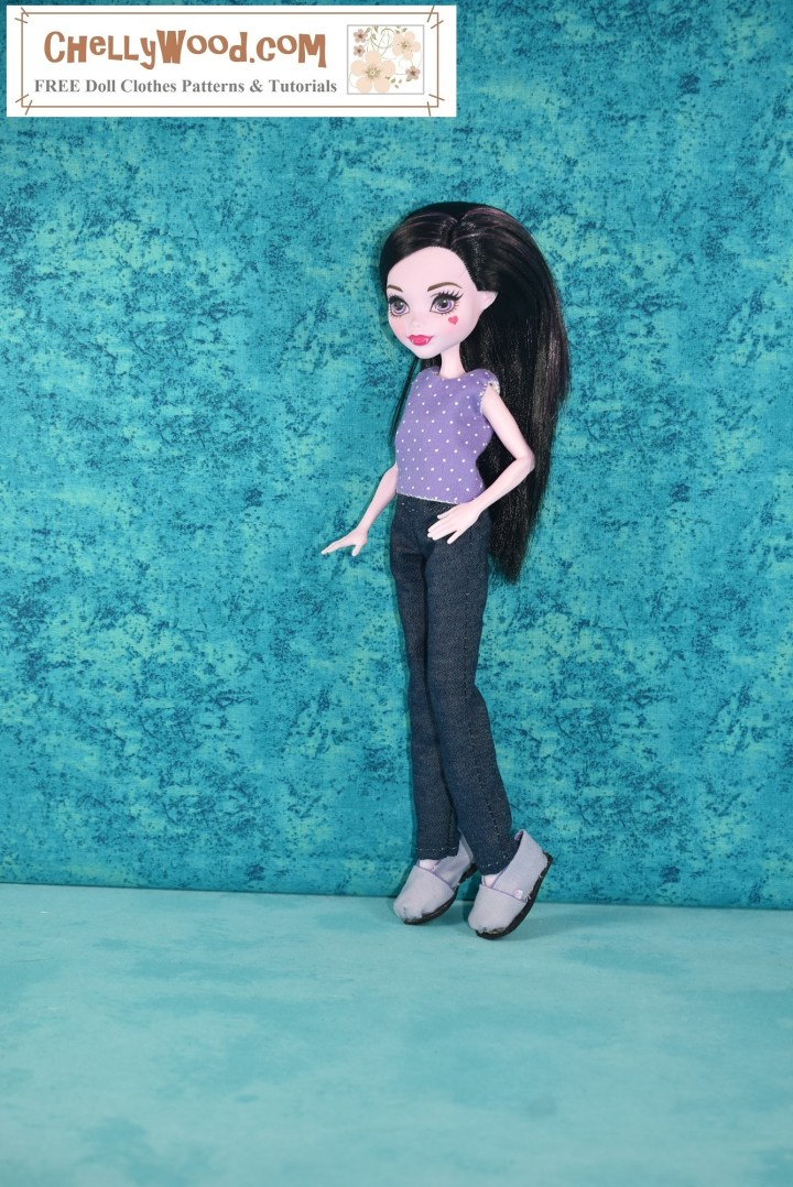 The image shows a Draculaura Monster High doll wearing a handmade crop top in purple cotton with tiny white polka dots over a pair of blue jeans. She stands in front of a turquoise blue background. The doll stands facing left of the camera with her left hand on her hip and her right hand slightly extended. Her left knee is bent. The watermark reminds you to visit ChellyWood.com for free printable PDF sewing patterns for making doll clothes to fit dolls of many shapes and all different sizes.