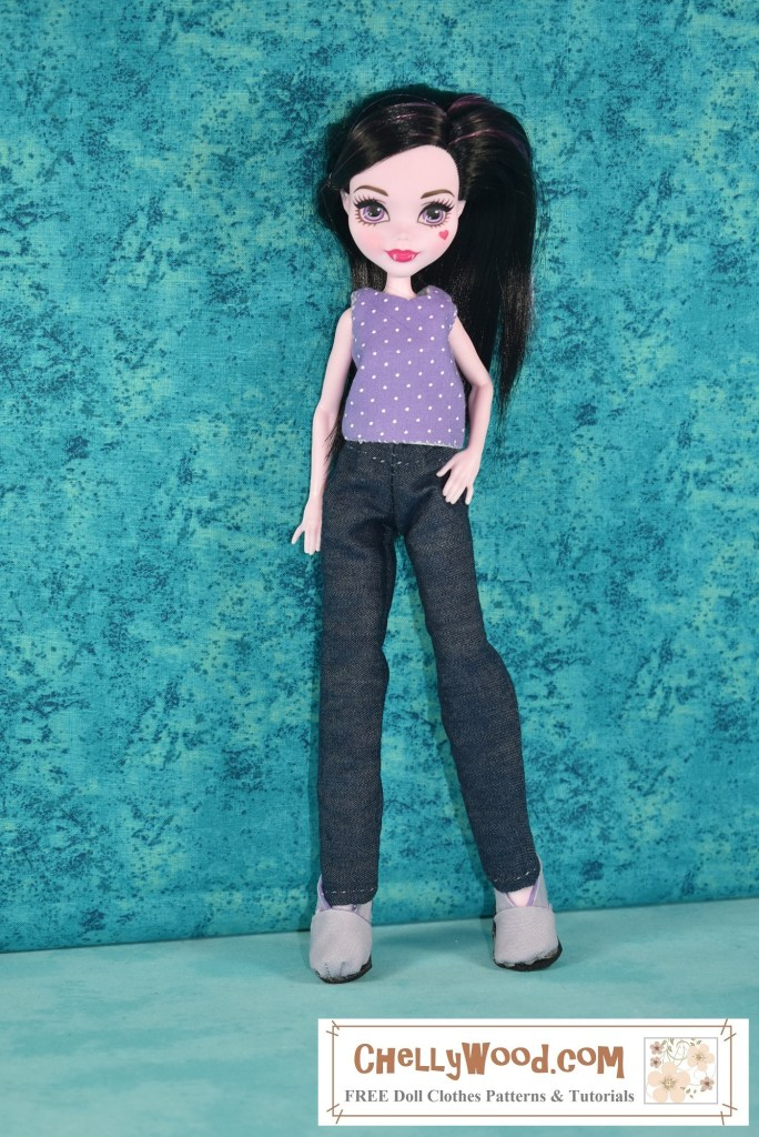 Please click the link in the caption to access the free printable PDF sewing patterns for making these doll clothes to fit your 10 inch Monster High or Ever After High fashion dolls (or similar sized dolls). This image shows a Draculaura Monster High doll facing the camera with her feet spread about an inch and a half (3.8 cm) apart. She wears a tiny crop top -tank-style shirt made of purple cotton fabric with tiny white polka dots dancing across the purple fabric, along with a pair of simple denim jeans (sometimes called dungarees). She stands with her right hand at her side and her left hand on her hip. The background behind her is a stonewashed or mottled turquoise blue fabric which contrasts against her pale pink skin, the bright purple of her crop top, and the deep dark blue--almost indigo -- denim of her jeans. Please remember to click on the link in the caption to navigate to the page where you can find the free printable PDF sewing patterns for making these doll clothes.