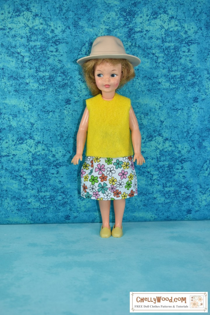 """In this photograph, the doll is facing forward. Here's a basic description of the doll in this photograph: we see a vintage Pepper doll (the vintage Tammy doll's little sister from the Ideal Toy Corporation) wearing a handmade floral cotton skirt and a handmade yellow felt sleeveless shirt. She also sports a pair of yellow loafers and a tan """"Indiana Jones-style"""" safari hat. This doll has reddish-colored hair in a bubble cut. Her freckles are barely noticeable, and she stands before a speckled turquoise blue background screen."""