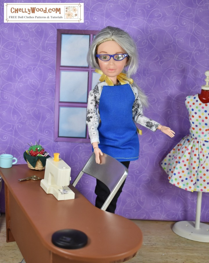 The image shows the Chelly Wood doll (actually a Spin Master Liv doll of the 1990's era which has been repainted and had her wig dyed grey to look like the real Chelly Wood) standing beside her sewing table with a blue apron on. Behind her on her left is a dress form, and on her sewing table is her tiny sewing machine. The dress form models a pretty party dress in white fabric with colorful polka dots. In one corner of Chelly's sewing table is a basket with fabric, notions, and a pincushion inside. There's also a light blue coffee cup on her desk. The wall behind her is purple and there's a window with glass-looking panes in the wall behind her. The overlay reminds you that this is ChellyWood.com, a website for free printable doll clothes sewing patterns.