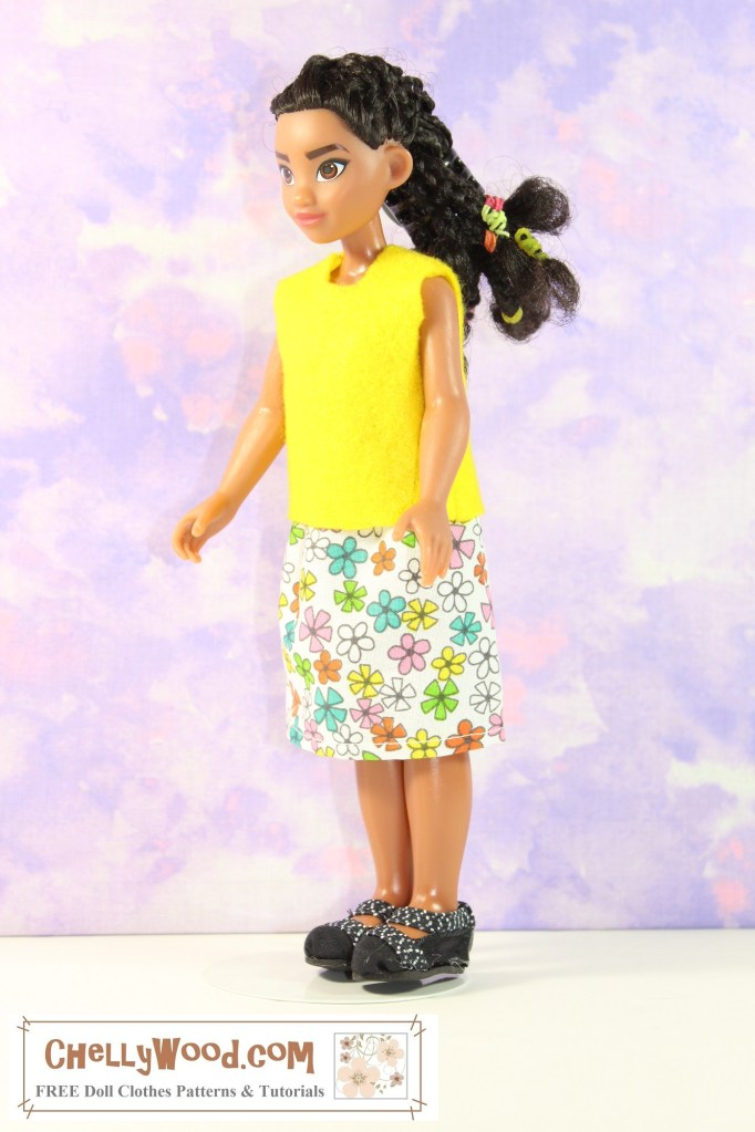 In this photograph a 10 inch Moana doll models her handmade shirt and shirt, which were made using free printable PDF sewing patterns from ChellyWood.com (a website which provides people with free patterns and tutorials for making doll clothes to fit dolls of many shapes and all different sizes). The felt shirt Moana wears is made of a bright yellow felt, and it is sleeveless. This springtime fresh color of yellow tops the multi-colored floral skirt the doll wears. She also wears a pair of handmade Mary Jane style black shoes. If you'd like to make a similar outfit of doll clothes for 10 inch Moana dolls or similar-sized dolls, please click on the link in the caption.