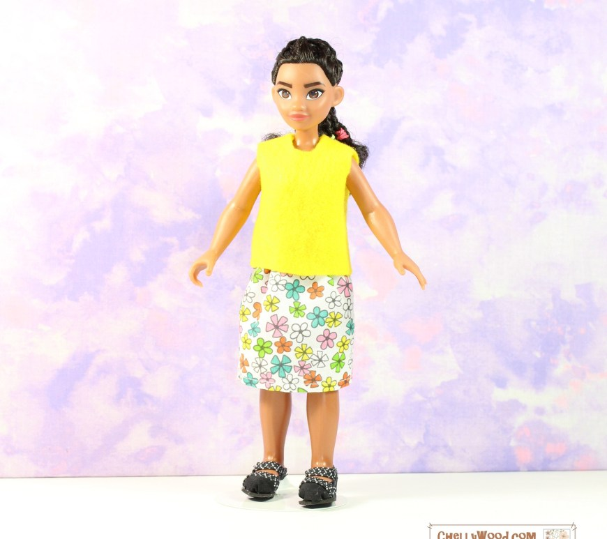 The image shows a very small Moana doll wearing a bright yellow felt sleeveless summer shirt over a multi-colored floral cotton skirt. The outfit looks quite simple to make. The URL provided on the image suggests that you visit ChellyWood.com for free printable doll clothes patterns and tutorials.