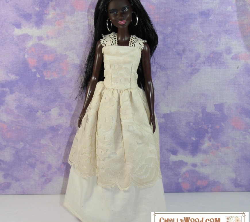 The image shows a modern African American or African fashion doll wearing a handmade wedding gown. The bodice of the dress is overlaid with off-white lace, and there's a layer of cream-covered lace over the top of the cotton skirting. The straps of the dress are also made of lacy off-white ribbon. This image represents the doll dress you can make with the free printable PDF sewing patterns found at ChellyWood.com (and incidentally, the website also offers free tutorial videos showing how to make this dress and variations of this dress).