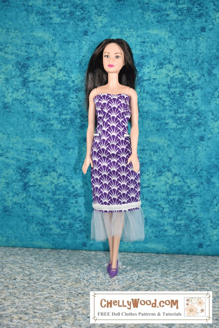 This image shows the front view of a Mattel modern Barbie doll wearing a handmade doll dress. This doll dress was sewn using McCalls Craft Pattern 4400. The fabric of the strapless dress is 100% cotton with a purple seashell print. The dress has a velvet ribbon around the bottom of it, with tulle trim at the edge of the dress. The photo was taken by Chelly Wood, whose website, ChellyWood.com offers free printable sewing patterns for dolls of many shapes and all different sizes.