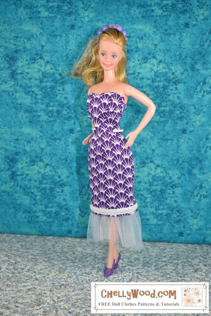 In this photograph, a vintage Super Star Barbie wears a strapless gown made of purple cotton fabric. The fabric is decorated with tiny white and purple seashells. The dress length (including the tulle ruffle at the bottom) is almost to the doll's ankles, with a slightly shorter ruffle in front than in the back. The ruffle is made of tulle. Above the ruffle is a white velvet strip of ribbon. Super Star Barbie looks curvy and voluptuous in this handmade dress. The watermark on the photo reminds you to visit Chelly Wood dot com for free patterns and tutorials.