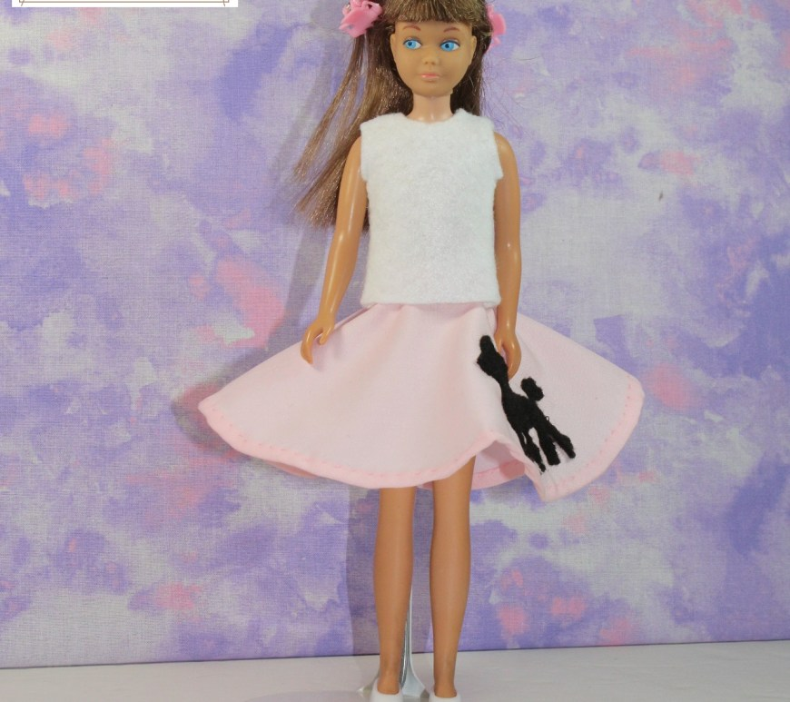 A skipper doll from the early 1970s wears handmade doll clothes that include a pink poodle skirt and a summer shirt. Her hair is pulled back with pink hair clips.