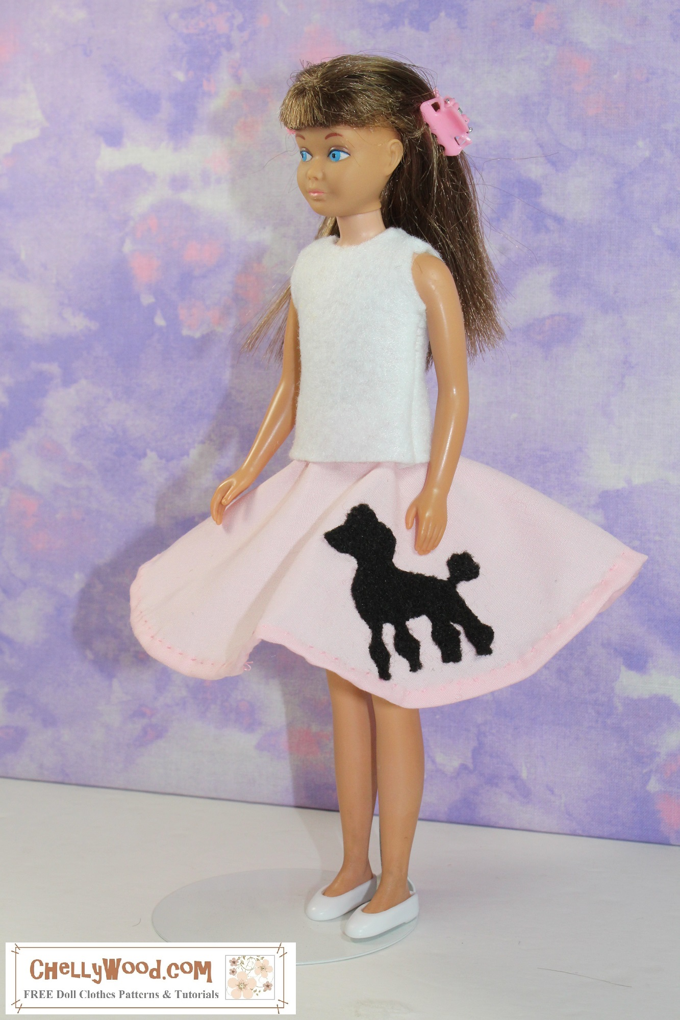 """The image shows a Mattel vintage Skipper doll wearing handmade doll clothes that include a felt sleeveless shirt and a pink poodle skirt that flares outward, as if vintage Skipper is spinning around. The overlay says, """"ChellyWood.com: free doll clothes patterns and tutorials,"""" reminding you to visit ChellyWood.com for your free printable sewing patterns for making doll clothes to fit dolls of many shapes and all different sizes. Would you like to make today's pink poodle skirt with a felt poodle patch sewn onto the skirt, along with the easy-to-sew felt sleeveless top? Please click on the link in the caption, and it will take you to the page where you can download and print the free printable PDF sewing patterns for making this outfit."""