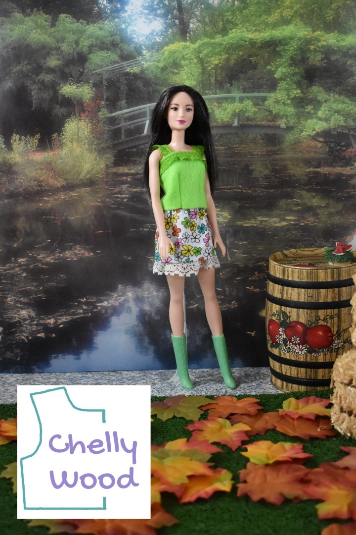 The image shows a modern Barbie modeling handmade doll clothes, including a lime green felt shirt with lace trim and lace straps along with a separate floral cotton skirt with lace trim. The doll's boots are green. She faces the camera, but her body appears to be walking toward a bale of hay in the foreground. Behind her is a pretty garden with a lake and a bridge that spans the lake.