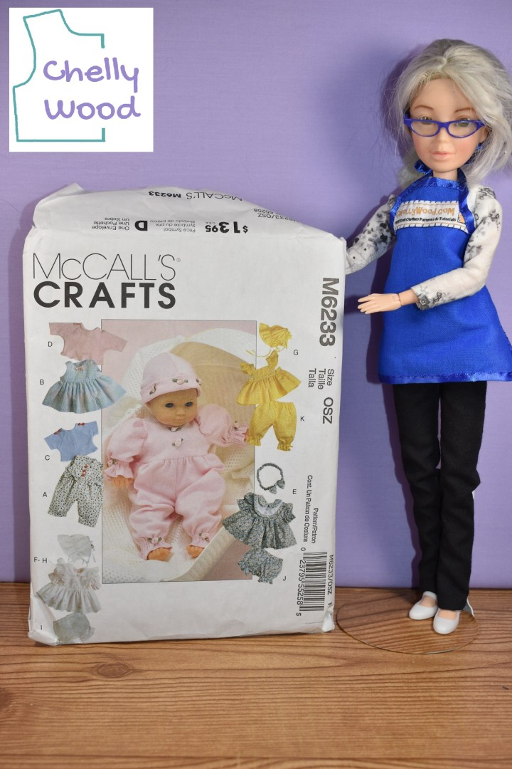 Here we see the Chelly Wood doll standing beside (and apparently holding up) the McCall's M6233 baby doll clothes pattern. Chelly Wood (represented here by a renovated Spin Master Liv doll) is a doll clothing designer, YouTuber, and writer. In today's article, she's discussing how to convert baby girl doll clothes patterns into baby boy doll clothes patterns. Visit ChellyWood.com to learn more.